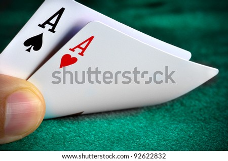 A man playing poker and checking his cards