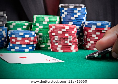 A man playing poker and raising his bet with two black chips