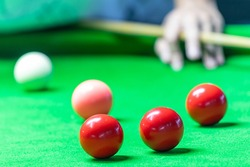 A man playing snooker in bar. Snooker player aiming snooker ball on snooker table.