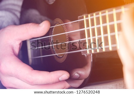 a man plays a small instrument, a hand leads along the strings, strings from a guitar