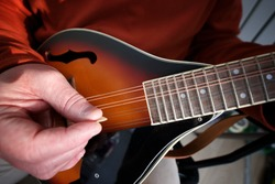 A man plays his Eight string mandolin at home during lock down