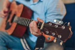 a man plays the guitar. hands hold the neck of the guitar. the musician is playing a tune.