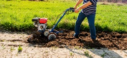 A man plows the ground with a tillerblock in the garden. Agricultural work.