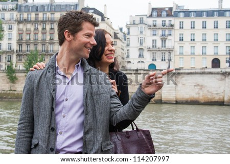 A man pointing to something, while a woman looks on and laughs.