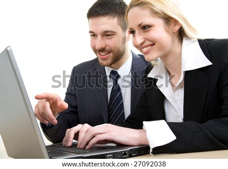 A man points at a screen of a laptop and a woman looks at it