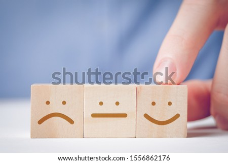 A man points his finger at a wooden cube with a positive face next to a neutral and displeased. Concept for evaluating an action or resource. Close up.