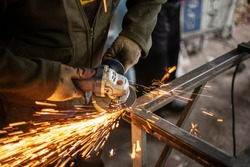 A man polishes metal in a workshop. Creation of an advertising structure. Metal frame in the garage. Sparks from metal cutting. Vivid flashes he split parts and due to friction.