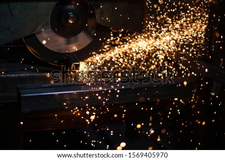 A man polishes metal in a workshop. Creation of an advertising structure. Metal frame in the garage. Sparks from metal cutting. Vivid flashes he split parts and due to friction. #1569405970