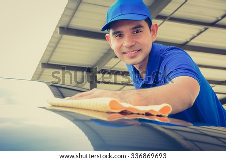 A man polishing car with microfiber cloth, car detailing or valeting concept - face focused, vintage tone