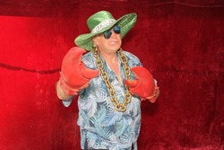 A man poses for photos in a Photo Booth. A man wears Lobster Claw Gloves and a Pimp Hat in a photo booth.