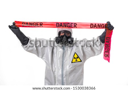 A man poses in a  silver protective suit with a red protective tape over his head. Protection. Danger.