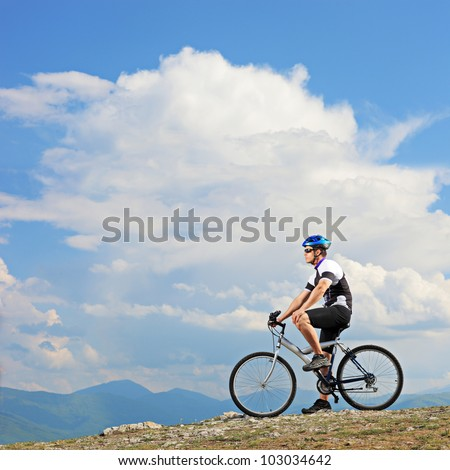 A man posing with a mountain bike on a ridge in Macedonia