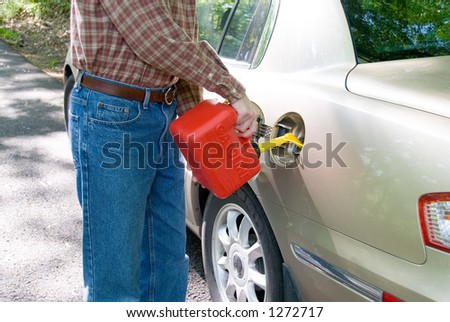 A man pouring gasoline into his tank from a red gas can.