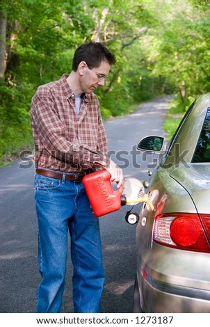 A man pouring gasoline into the gas tank of his car from  a red gas can.  He's standing on a country road in the  middle of nowhere, lost.