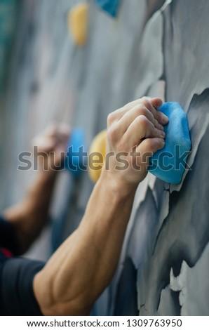 A man practicing rock-climbing on a rock climbing wall #1309763950