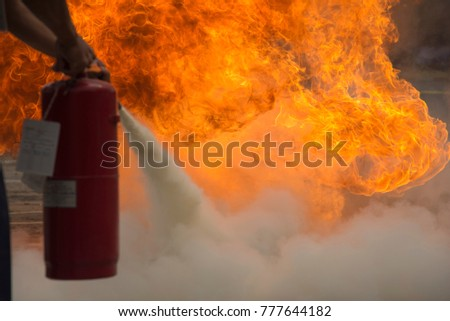 A man practises how to use a fire-extinguisher Stockfoto ©