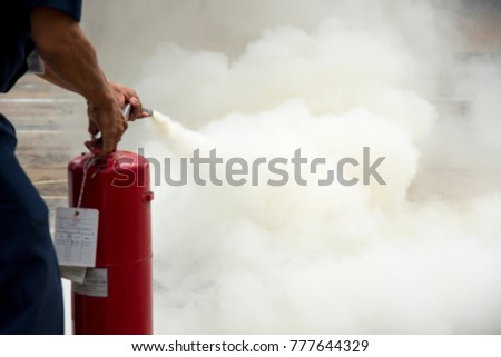 A man practises how to use a fire-extinguisher