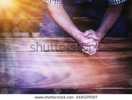 a man pray on wooden table with ...