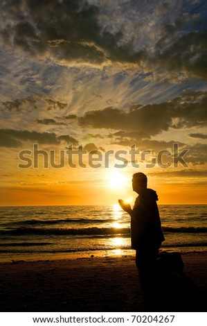 A man praying at the ocean while watching a glorious sunset.