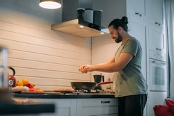 A man prepares breakfast in the kitchen. Young handsome caucasian male preparing food for himself for lunch on a gas stove in a large bright kitchen