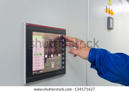 A man presses a button on color screen control of equipment for telecom.