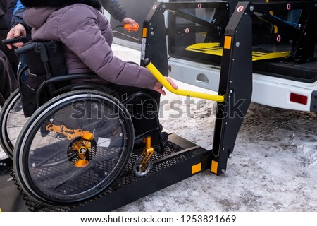 A man presses a button on the control panel to pick up a woman in a wheelchair in a taxi for the disabled. Black lift specialized vehicle for people with disabilities. Yellow handrail. Winter time.