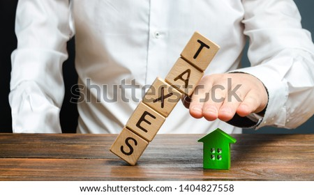 A man protects his hand with a figurine of a house from a falling tower of cubes with the word taxes. Heavy tax burden, protecting the interests of small and medium-sized businesses, competitiveness. Stock photo ©