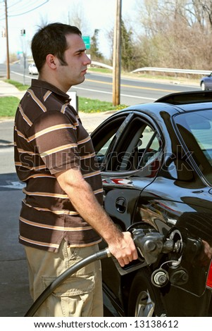 A man pumping high priced gas into his car with a disgusted look on his face. - stock photo