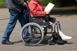 A man pushing a woman in a wheelchair with a injured leg