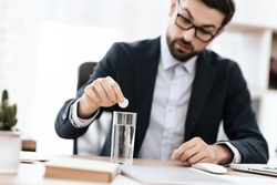A man puts a pill into the water while sitting at a table. A man throws painkillers into the water while sitting at a table.