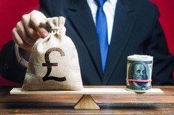 A man puts a pound sterling GBP money bag on the scales opposite to the dollar. Exchange rate, comparison of economic indicators. Investments in foreign currency bonds. Avoiding savings inflation.