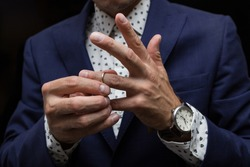 a man puts a wedding ring on his finger, the concept of cheating on a married man.