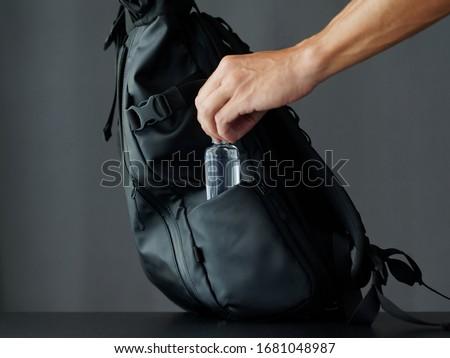A man puts alcohol gel in a black modern backpack. Sanitizer  Stock foto ©