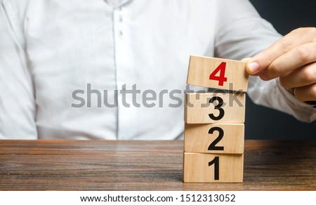 A man puts numbered wooden blocks on top of each other. Alternate items and conditions for implementation. Contract road map. Organization and systematization, step by step instructions. Stock photo ©