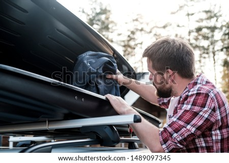 A man puts things in the roof rack of a car or in a cargo box, on a blurred background of a house and trees, on a summer evening. Joint family trip. Close-up. #1489097345