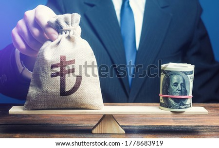 A man puts turkish lira money bag on the scales opposite to the dollar. Protecting savings from inflation. Investments in foreign currency bonds. Exchange rate, comparison of economic indicators.