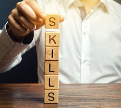 A man puts wooden blocks with the word Skills. Knowledge and skill. Self improvement. Education concept. Training. Leadership skills. Human abilities