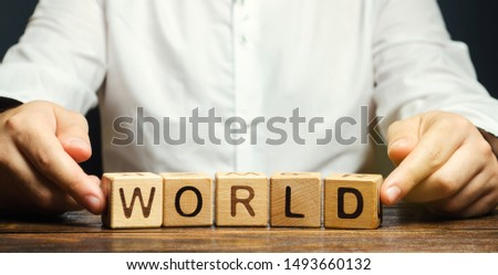 A man puts wooden blocks with the word World. The concept of globalization and global business. International relationships. Diplomacy. Investments and economics. Geography #1493660132