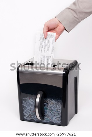 A man putting confidential documents into a paper shredder