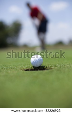 A man putts a golf ball on the green.
