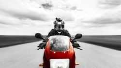 A man quickly rides on the road to the camera on a red motorcycle. Black and white photo