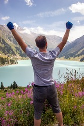 A man raised his hands to the sky next to a mountain lake. Spectacular scenic on Big Almaty Lake ,Tien-Shan Mountains in Almaty region of Kazakhstan. Vertical