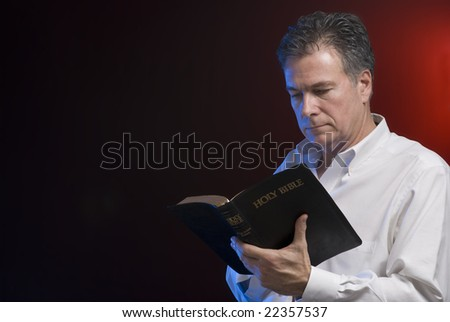 A man reading a bible, background and side lighting with red and blue gels.