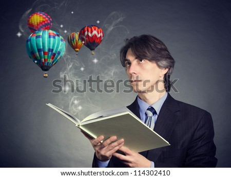 A man reading a book and imagining the balloons in the sky.