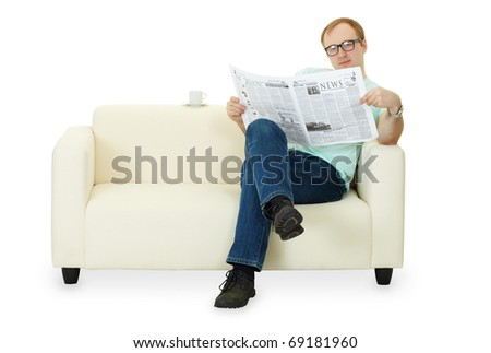A man reading a newspaper at home sitting on the sofa - stock photo