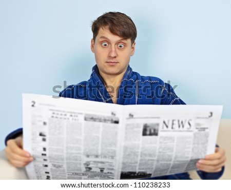 A man reads a newspaper with a amazement