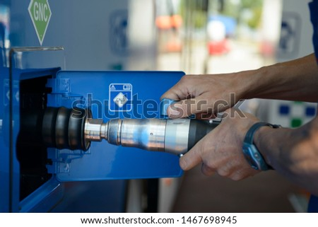 A man recharges a vehicle with compressed natural gas fuel, ecological fuel known as CNG #1467698945
