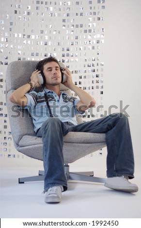 a man relaxes in a chair listening to music