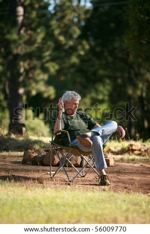 a man relaxes outside as he does a crossword puzzle and communes with nature
