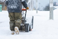a man removes snow with a snow plow after a heavy snowfall near his house, close-up, blizzard, snow in the lens, selective focus, snow